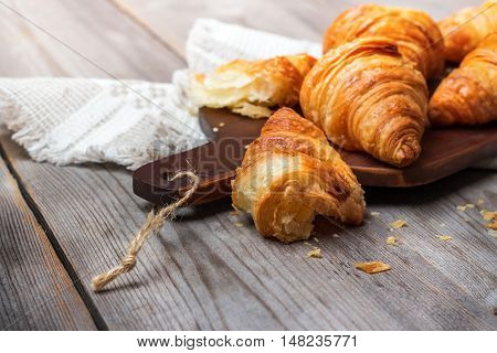 Food and drink, still life concept. Fresh croissants for breakfast on a rustic wooden table. Selective focus