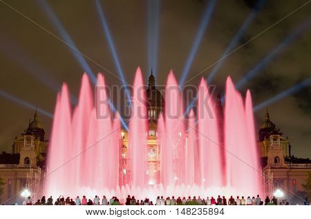 BARCELONA - SEPTEMBER 19, 2014: Night view of Magic Fountain light show in Barcelona, Catalonia, Spain. Magic fountain of Montjuic light show at Plaza Espanya in Barcelona with people silhouette on bottom.
