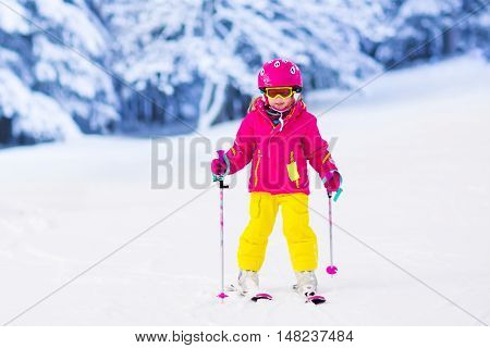 Child skiing in mountains. Active toddler kid with safety helmet goggles and poles. Ski race for young children. Winter sport for family. Kids ski lesson in alpine school. Little skier racing in snow poster