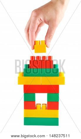 Hand building the toy house isolated on white