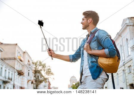 Smiling young casual man making selfie with smartphone and selfie stick at the city centre