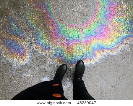View of black boots on oil spill