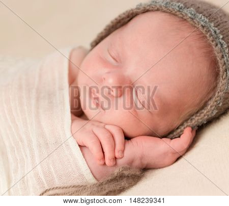 lovely face of sleepy swaddled newborn baby in knitted hat