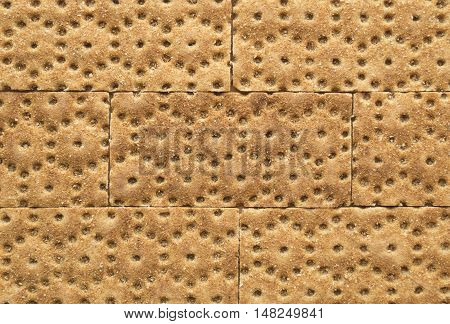 Crisp rye bran bread texture background with brickwork