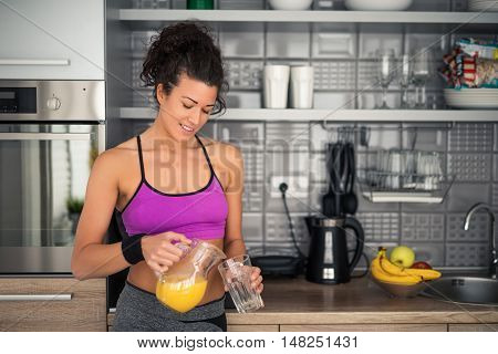 Portrait of a young female athlete sipping orange juice.
