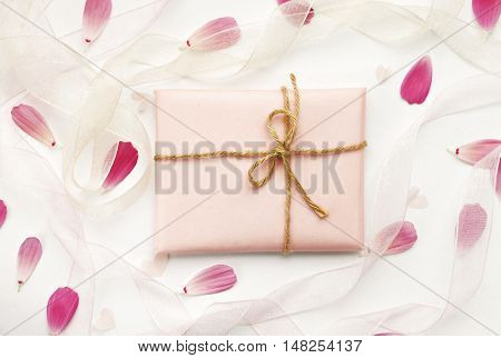 handiwork gift wrapped in pink paper with twine bow, arranged amidst flower petals and ribbons. Dreamy soft congratulation background.