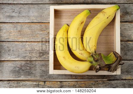 banch of bananas in wood box on wood table