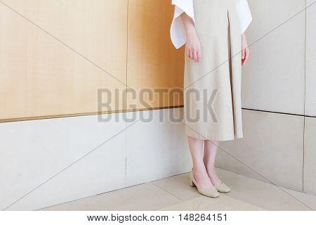 woman standing in corner beige dress with mid heel shoe minimal style.