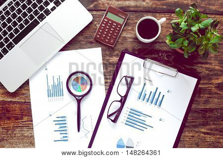 workplace economist with laptop and graphics on office table top view