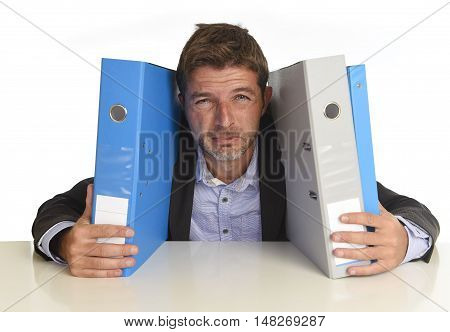 young attractive busy businessman overwhelmed suffering crazy stress at office looking sad and desperate holding paperwork folders on desk in business frustration and overwork problem