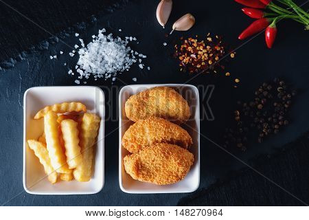 Nuggets and fries on a black stone plate