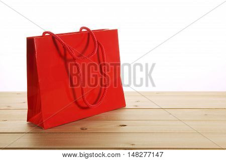 Red Shopping Paper Bag on Wooden Background