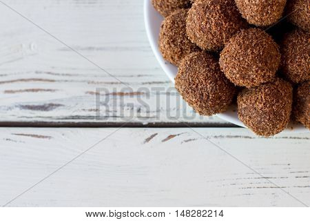 Top view of brown sweets. Dark candies on wooden background. Proven recipe of chocolate balls. Biscuits and cocoa powder.