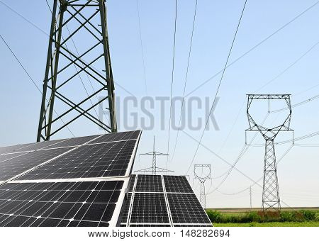 Solar panels with electricity pylons. Concept of sustainable resources.