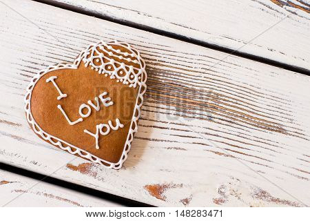 Heart shaped cookie with inscription. Biscuit of brown color. Convey message through a gift. Confession in love.