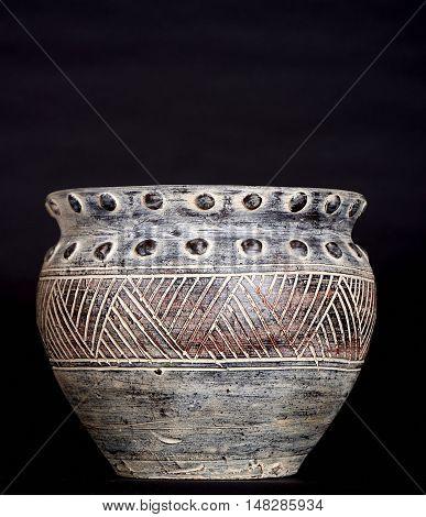 gray vase/urn photographed on seamless black paper background