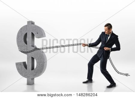 Businessman pulling big concrete 3d dollar sign with a rope isolated on white background. Making money. Success and profit. Hard work.