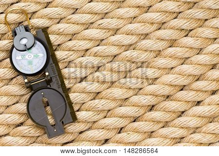 Single Nautical Compass Over Thick Rope Background