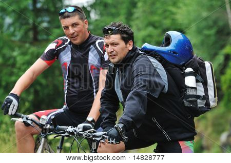 two friends have fun outdoor in nature and representing concept of  healthy life and fitness on mountain bike