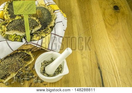 Basket with sunflowers and mortar with crushed seeds - White mortar with the pestle and crushed sunflower seeds inside in autumnal settings.
