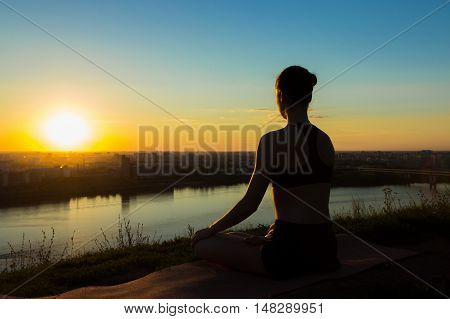 Sporty woman in lotus position in the park at sunset. Sunset light, golden hour, lens flares. Freedom, health and yoga concept.