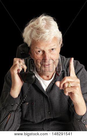 Senior gentleman talking on a vintage phone.