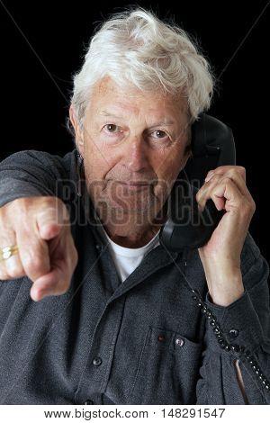 Senior gentleman pointing while talking on a vintage phone.