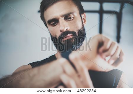 Portrait Bearded Sportive Man After Workout Session Checks Fitness Results Smart Watch.Adult Guy Wears Sport Tracker Wristband Arm.Training hard inside gym.Horizontal bar background.Blurred
