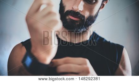 Close-up Shot Young Bearded Sportive Man After Workout Session Checks Fitness Results Smart Watch.Adult Guy Athlete Wearing Sport Tracker Black Tshirt.Training hard gym.Horizontal.Blurred background poster