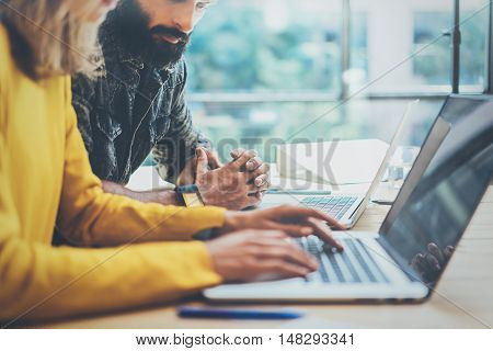 Two Modern Coworkers Discussing Together During Working Process.Young Business People Meeting Concept.Discussion Startup Project Office.Bearded Man Looking Laptop, Woman Typing Wood Desk Table.Blurred