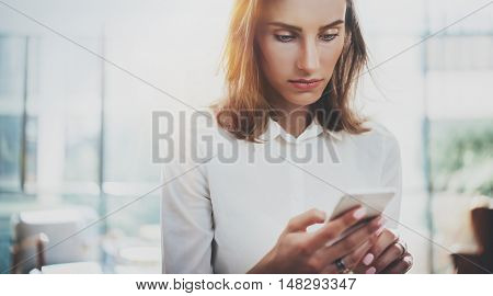 Portrait young business woman wearing white shirt using modern smartphone hands.Girl texting sms message working process.Sunny space loft office.Panoramic windows background.Horizontal blurred