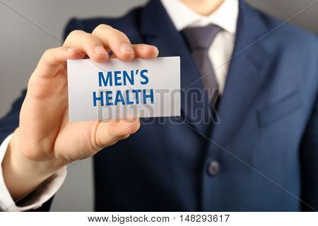 Businessman with business card, close-up. Urology concept