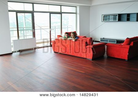 happy couple relaxing on red sofa in big bright new apartment