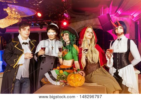 Group of friends in halloween costumes having party in the night club
