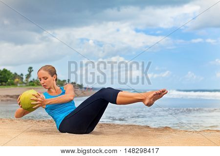 Fit woman stomach exercising on sand beach. Doing crunches core leg raising and twisting exercises with coconut as weight. Woman doing abs workout. Fitness woman doing a sit up. Ocean surf background