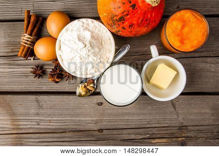 Selection of ingredients for making a traditional pumpkin pie for Thanksgiving or Halloween. At the rustic wooden table, top view, copy space