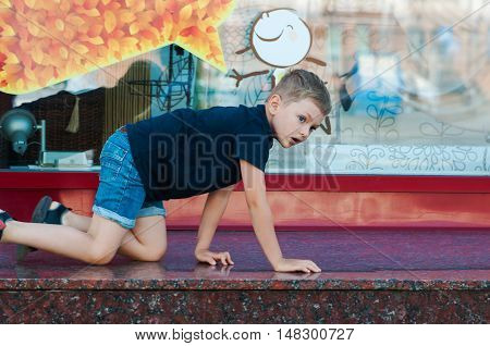 Caucasian boy crawling along the storefront outdoor