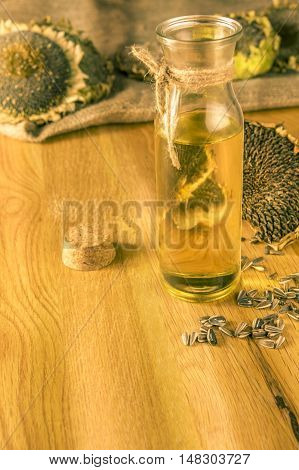 Sunflower oil on a wooden table - Bottle with cold pressed oil on a wooden table with sunflower plants and seeds all over it