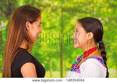 Two beautiful young women posing for camera, one wearing traditional andean clothing, the other in casual clothes, both smiling, staring into each others eyes, seen from profile angle, park background.