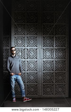 Trendy man with suglasses stands on the background of the carved door casual concept structure
