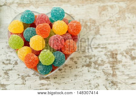 Sweet heart with jellybeans on a wooden background