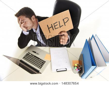 young desperate businessman suffering stress working at office computer desk holding sign asking for help looking tired exhausted and overwhelmed by heavy work load