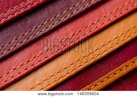 Leather samples with stitches, natural materials with seams of red, maroon, brown, orange colors and other warm shades, women's bag detail, macro shot, selective focus