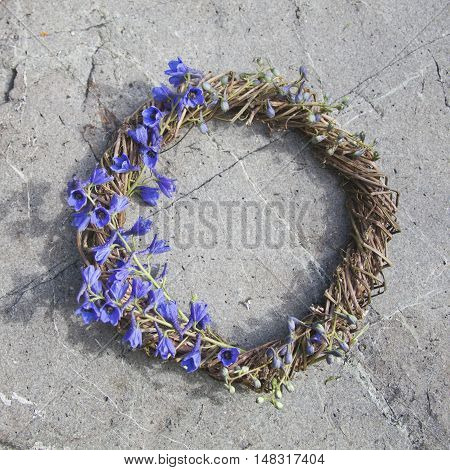 Wreath with blue larkspur high flowers on a stone background