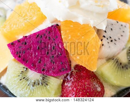 Closeup of fruits in Bingsu. Bingsu is local Korean shaved ice dessert serve with toppings such as chopped fruit mango orange kiwi strawberry dragon fruit and berry syrup.