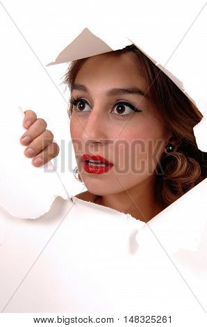 The face of a beautiful young woman showing trough a hole in the paper with big eyes isolated for white background.