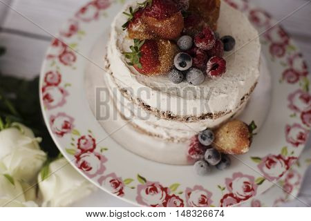 Naked Cake With Caramelized Fruits - Strawberries, Blueberries, Raspberries. Sponge Cream Cake In Fl