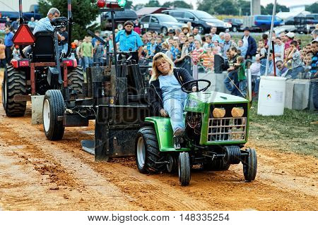 MYERSTOWN PENNSYLVANIA - SEPTEMBER 16 2016: A woman drives a modified lawn tractor at Myerstown East End Days. The tractor pull is an annual community event.