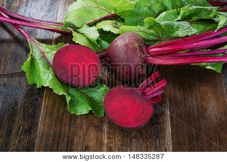 Fresh beetroots with leaves on wooden rustic table.Whole and cut beetroots