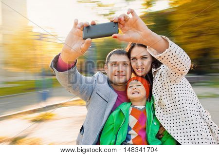 Family having fun on spinning roundabout. selfie Portrait. Naturally blur motion